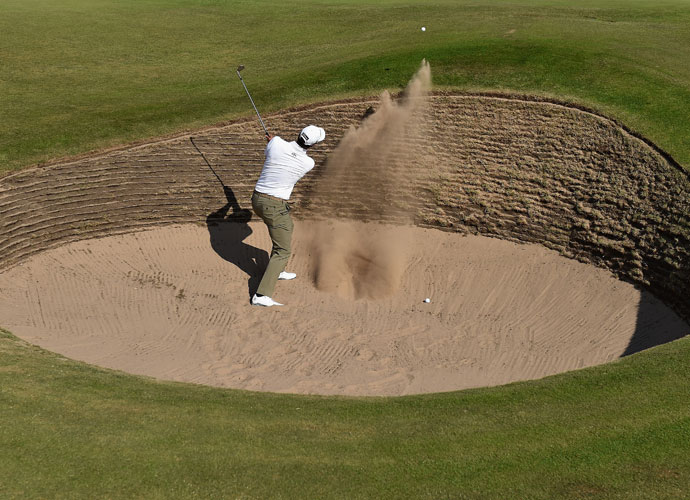 Adam Scott hits his third shot from a bunker on the tenth hole. He parred the par 5.