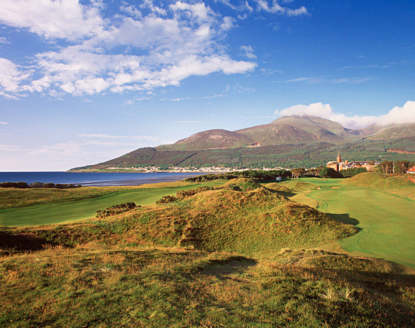 Hole No. 3                   Royal County Down                   Newcastle, Northern Ireland                   9th hole; par 4, 486 yards                                      Rising in the backdrop beyond the red brick steeple of the Slieve Donard Hotel are the Mountains of Mourne, while to the left sits Dundrum Bay and the Irish Sea. The daunting tee shot is to a blind fairway that is framed with gorse bushes 80 feet below you. The approach is only marginally easier, with a pair of bunkers etched into a slope 25 yards short of the elevated green. Three more whiskered traps stand guard closer to the surface. In the wind, no hole on earth better combines beauty and brawn.