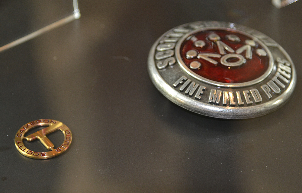 Ball markers and belt buckles like these on display in the lobby of Cameron's building are highly-prized by collectors.