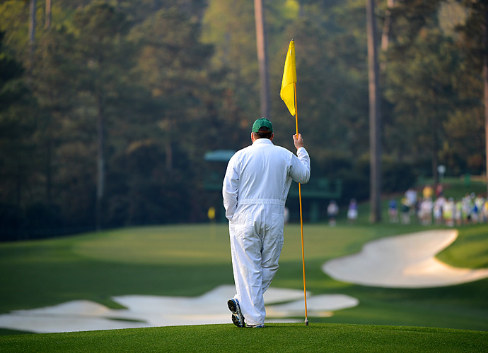 A caddie dressed in his white Augusta jumpsuit stands overlooking the course.