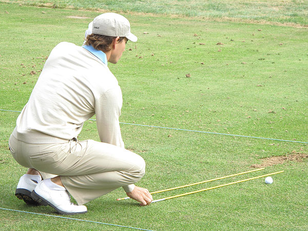 carefully positioned two rods on the range to help him practice proper alignment.