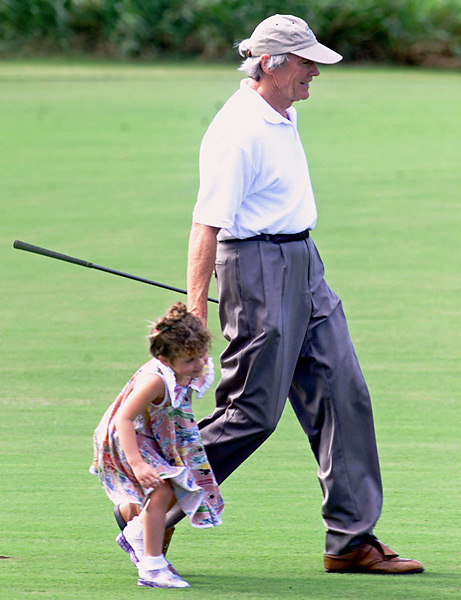 Actor Clint Eastwood walks hand-in-hand to the 18th green with his daughter, Morgan, 3, during the Pro-Am of the Mercedes Championships played at the Plantation Golf course in Kapalua, Hawaii, Wednesday, Jan. 10, 2001.