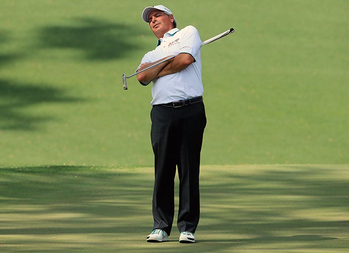 Fred Couples stretches as he waits to putt on the 10th green.