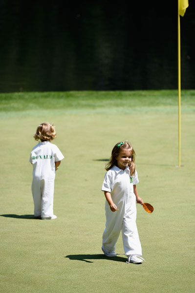 Elle and Sophia Ann, daughters of Luke Donald, walk on the ninth green.