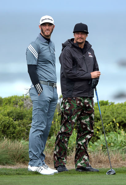 Dustin Johnson and Kid Rock wait to play the 13th hole during the second round.