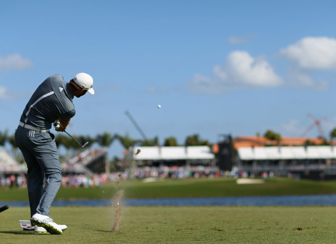 Dustin Johnson hits his tee shot on the ninth hole during the wind-swept second round of the WGC-Cadillac Championship. He shot 73 to finish in a four-way tie for first with Hunter Mahan, Patrick Reed and Matt Kuchar.