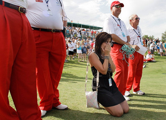 Ellie falls to her knees and cries between tournament volunteers by the 18th green after her husband won the 2010 Byron Nelson Championship.