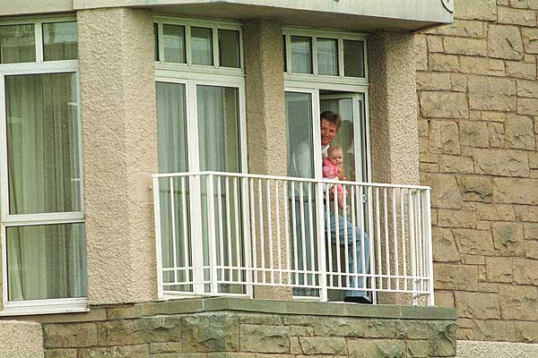 Holding his new daughter, Samantha, Els poked his head outside his room at the St. Andrews Hotel during the 1999 British Open.
