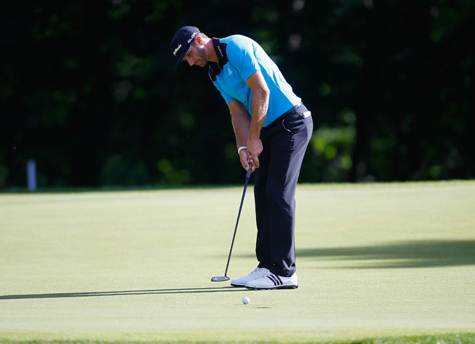 Dustin Johnson putts on the 11th hole during his second round 66. He's alone in ninth, three shots back.