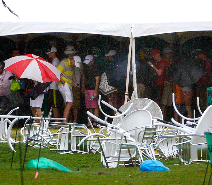 Spectators huddled under a tent alongside the first hole as the thunderstorm passed.