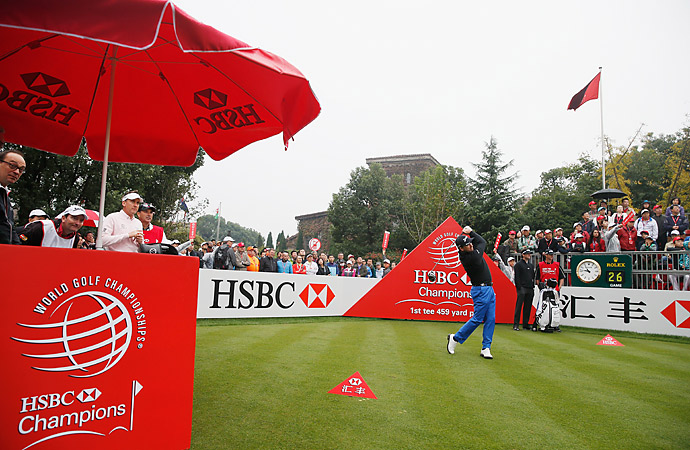 Ian Poulter and Bubba Watson look on as McDowell tees off on the first hole.