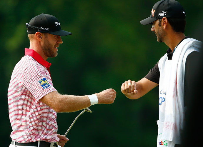 Canadian Graham DeLaet gets a fist-bump from his caddie after a birdie on 17. He shot 63 to get within two shots of the leaders.