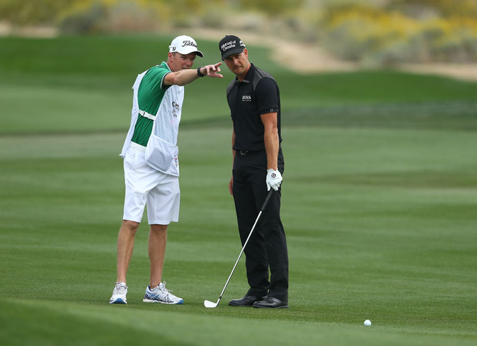 Top-seeded Henrik Stenson of Sweden confers with his caddie before playing a shot on the second hole. Stenson birdied the hole on the way to winning his first-round match, 2 and 1, over Kiradech Aphibarnrat.