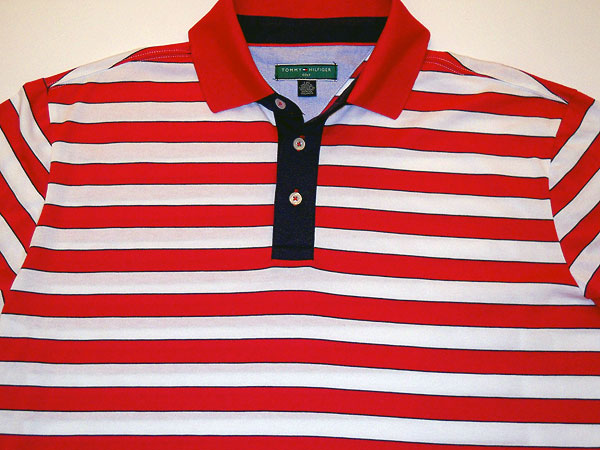 Tommy Hilfiger Golf Shirt                       After a six-year absence, Tommy Hilfiger is returning to American golf. The company had apparel on display at the PGA Expo in Las Vegas, like this performance cotton-blend polo in flag colors with an Oxford-blue collar lining, typical of Hilfiger's bold prep style.