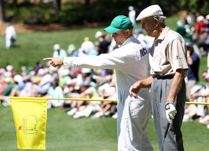 Jack Fleck looks over a green with his caddie during the par 3 contest prior to the 2011 Masters Tournament.