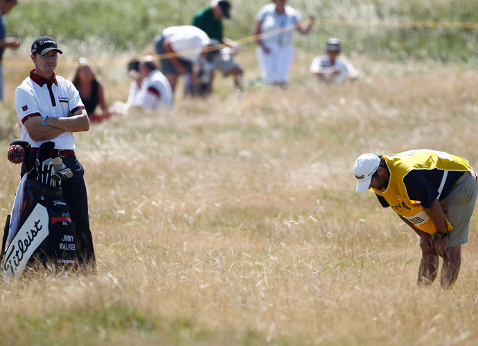 Jimmy Walker's caddie gets a good look at Walker's lie in the fescue. Walker shot a three-under 69.
