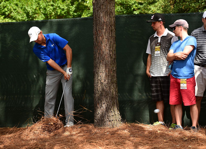 "Jordan Spieth punches from the pine straw back to the fairway in his opening round.  ""It's not fun to play out of the weeds,"" he said. ""But got it around."""