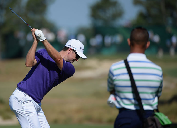 Justin Rose hits a shot as instructor Sean Foley watches his form during a practice round.