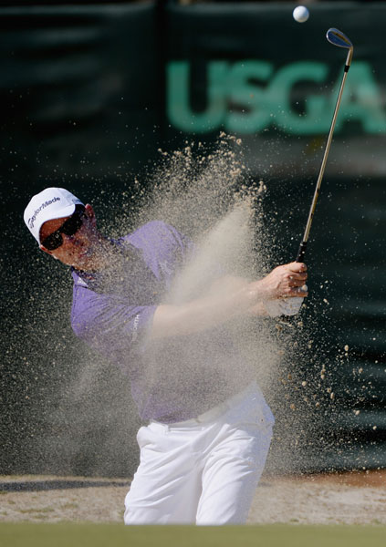 Defending champion Justin Rose escapes from a greenside bunker during his practice round.