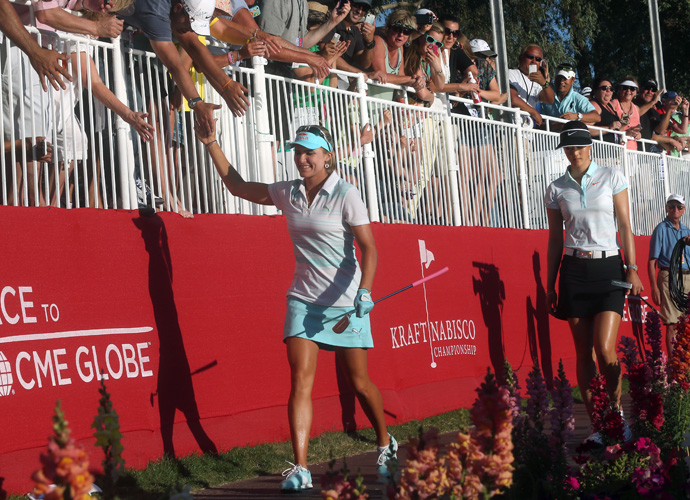 Thompson and Wie walk past the grandstand on their way to the 18th green.