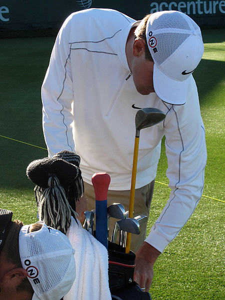 warms up by swinging a Medicus weighted driver (the yellow-shafted club), but also carries a SwingStick, another weighted warm-up tool that has a handle like a baseball bat.
