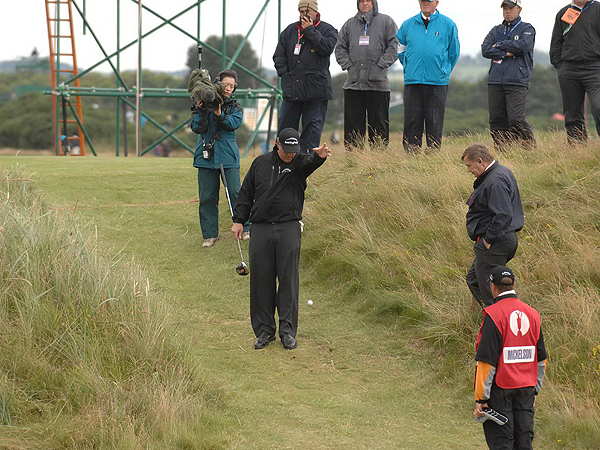 """Phil Mickelson's second shot on No. 2 plugged in the rough. He took a penalty stroke and dropped the ball, but it rolled closer to the hole, so he was allowed to place the ball. After it was deemed """"in play,"""" it rolled about 10 feet closer to the hole. Mickelson, by rule, played the ball from where it came to rest on the edge of the green and salvaged a bogey. He shot 77 and missed the cut."""