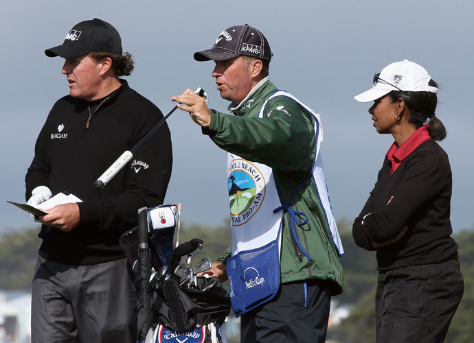 Phil Mickelson, caddie Jim Mackay, and former Secretary of State Condoleezza Rice wait on the 13th tee.