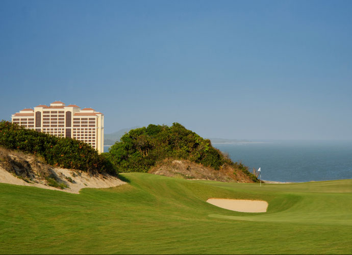 """The Grand resort can be seen in the distance from the 157-yard par-3 11th hole. The 541-room, 20-story beachfront hotel features world class dining and casino gaming. It opened in July 2013 as Vietnam's first international luxury casino. """"When players go somewhere, what we like to have are the creature comforts, and you certainly have those here,"""" Norman said."""