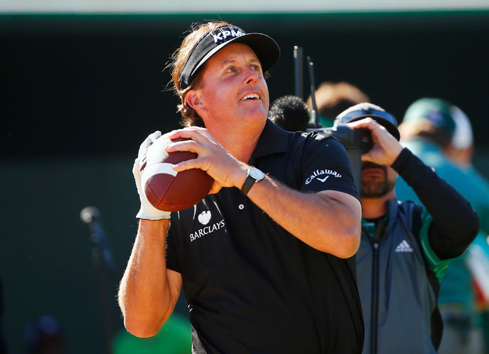 Phil Mickelson gets ready to throw an autographed football into the crowd on the 16th hole Saturday during the third round of the Waste Management Phoenix Open.