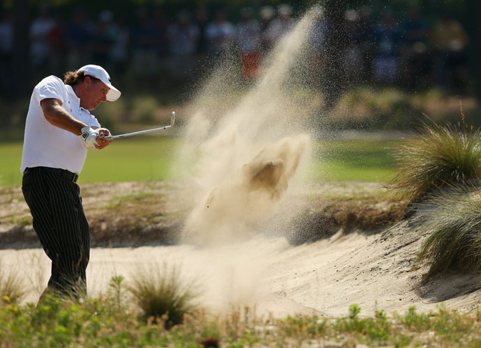 Phil Mickelson blasts out of a fairway bunker during his practice session.