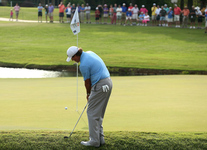Phil Mickelson chips onto the green on the 11th hole. He got up and down for a par.