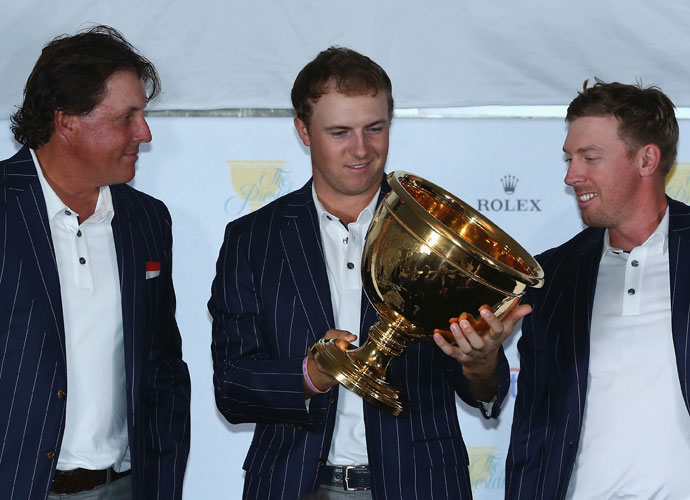 Jordan Spieth, flanked by Phil Mickelson and Hunter Mahan, admires his first piece of Presidents Cup hardware.