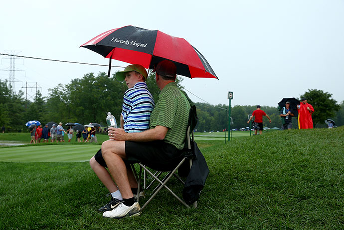 Fans walk in the rain during a weather-delayed final round of the 96th PGA Championship at Valhalla Golf Club.
