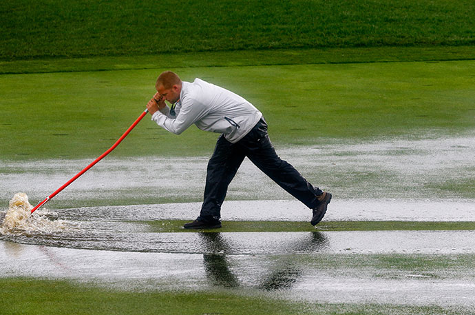 A member of the grounds crew squeegees the first fairway during a weather-delayed final round of the 96th PGA Championship at Valhalla Golf Club.