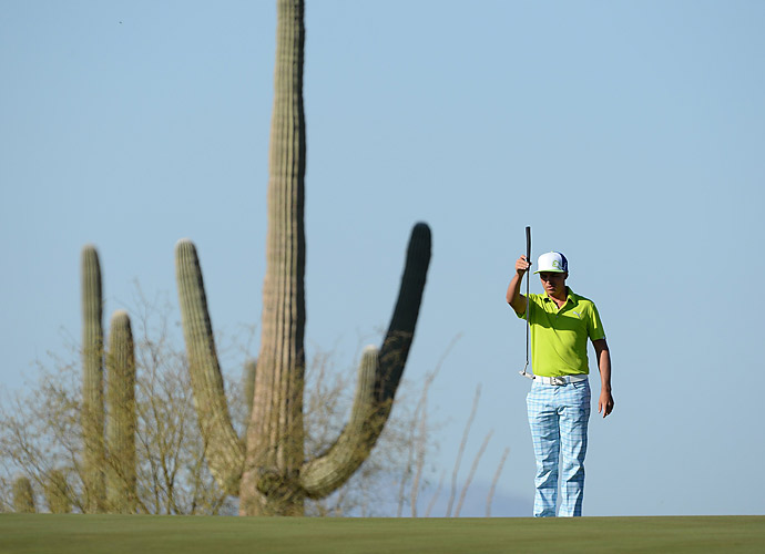 A cactus towers over Fowler as he lines up a putt on Thursday.