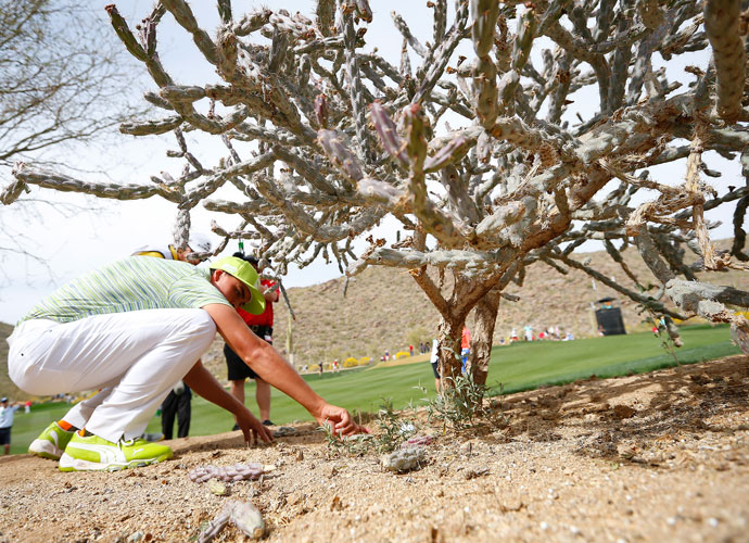 Rickie Fowler cleans the area around his ball before his second shot on the 15th hole.