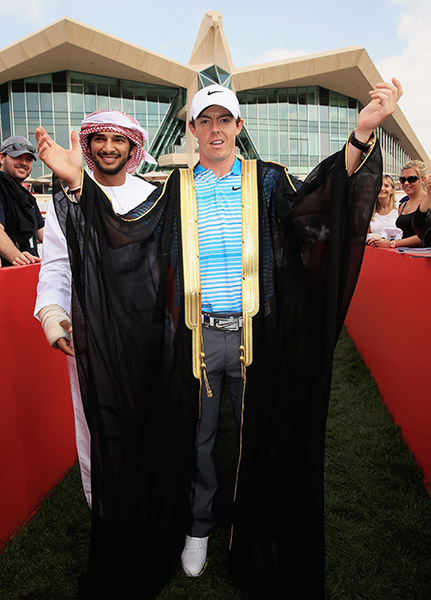Adal Khalid of Abu Dhabi Ocean Racing presents Rory McIlroy of Northern Ireland with a traditional Emirate 'Bisht,' a gown given as a gift to men who have recently become engaged.