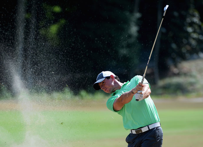 Rory McIlroy hits a shot from a bunker during a practice round. A rules official will accompany each group once play begins and can issue rulings on whether a player's ball is in a bunker or a waste area.