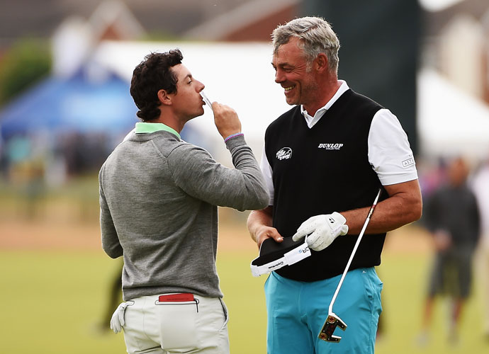Rory McIlroy kisses his winnings after collecting them from Darren Clarke.