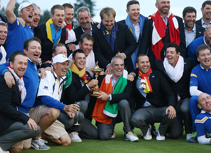 Adorned with their countries' flags, Team Europe poses with captain Paul McGinley after winning the 40th Ryder Cup.