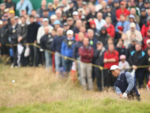 Woods hit his second shot on the par-5 14th over the Spectacles bunkers and into the rough short and right of the green. He hit a low, high-spin shot that skidded to a stop 10 feet from the hole, but he missed the putt and settled for par.