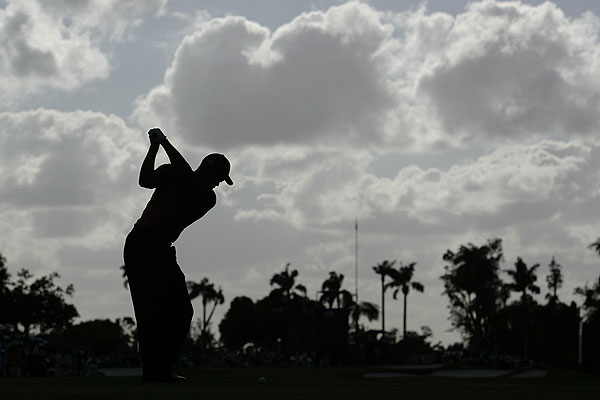 """As he hit his tee shot on the 13th at Doral, it was the perfect time to silhouette Woods. The palm trees in the background add a sense of 'Florida.' To get the image, I had to lie down with the camera just inches from the ground."""