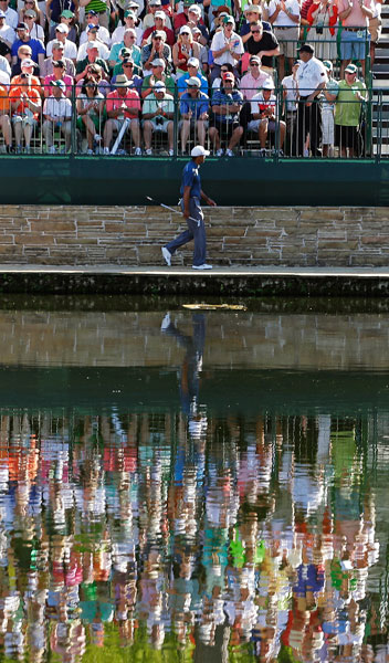 Tiger Woods walks to the 15th green during the third round of the 2013 Masters. He shot 70-73-70-70 to finish -5. He announced Tuesday he will miss the 2014 Masters while he recovers from successful back surgery.