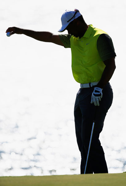 Tiger Woods takes a drop after hitting his ball into the water on the third hole in the second round. More than 100 balls found the drink in the wind-swept second round.