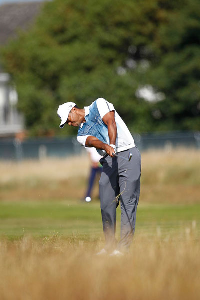 """Tiger Woods rips a shot from the fescue. """"I felt good about a lot of things I did out there today,"""" he said after his opening round."""