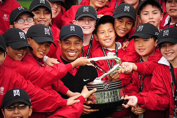 With the win, Woods tied Arnold Palmer on the career victory list at 62. Afterward, he celebrated with children from the Tiger Woods Foundation.
