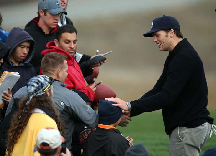New England Patriots quarterback Tom Brady signs autographs for fans on the 12th hole during the second round.