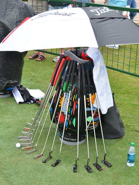During the intermittent rain storms, tour reps had to keep the putters on the practice green dry.