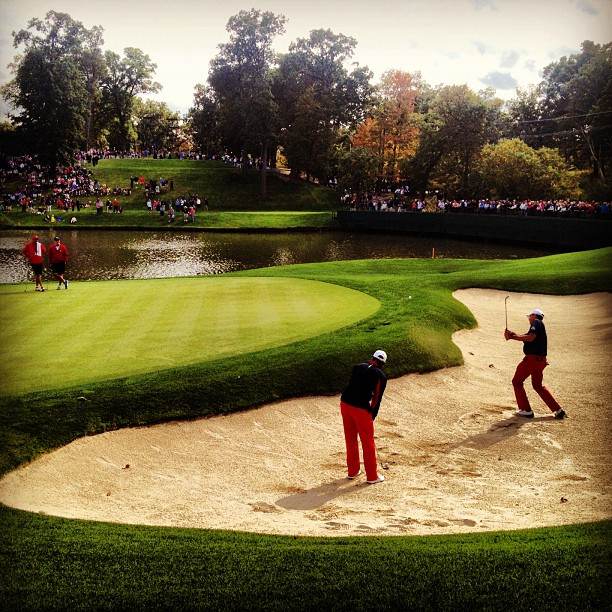 @stephaniemwei:Kuchar and Tiger practicing dozens of bunker shots on 17.