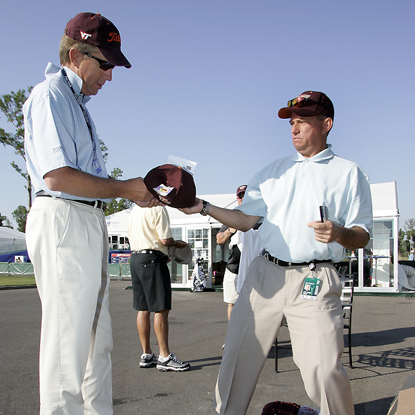 PGA Tour Media Official Joe Chemycz, right, gives a Virginia Tech hat to Dan Forsman before Saturday's third round.